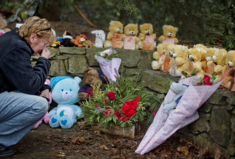 Cheryl Girardi, of Middletown, Conn., kneels beside 26 teddy bears, each representing a victim of the Sandy Hook Elementary School shooting, at a sidewalk memorial, Sunday, Dec. 16, 2012, in Newtown, Conn. (David Goldman/AP)