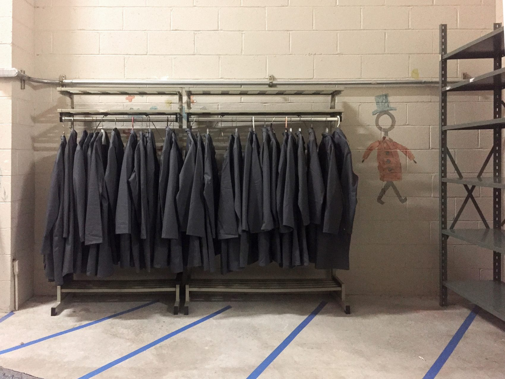 "A rack holds gray lab coats, ready for the ""Waiting Rooms"" attendants to wear. (Courtesy Nathalie Pozzi/Museum of Science)"