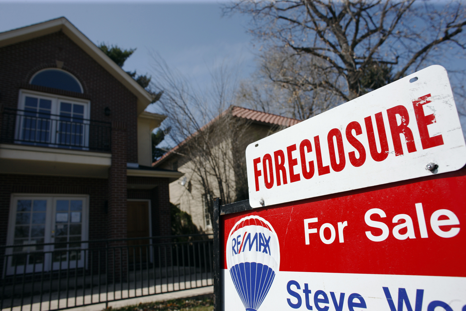 In this April 4, 2010 file photo, a foreclosure sign sits atop a for sale sign in front of a single-family home tops the for sale sign in Denver on Sunday, April 4, 2010. (David Zalubowski/AP)