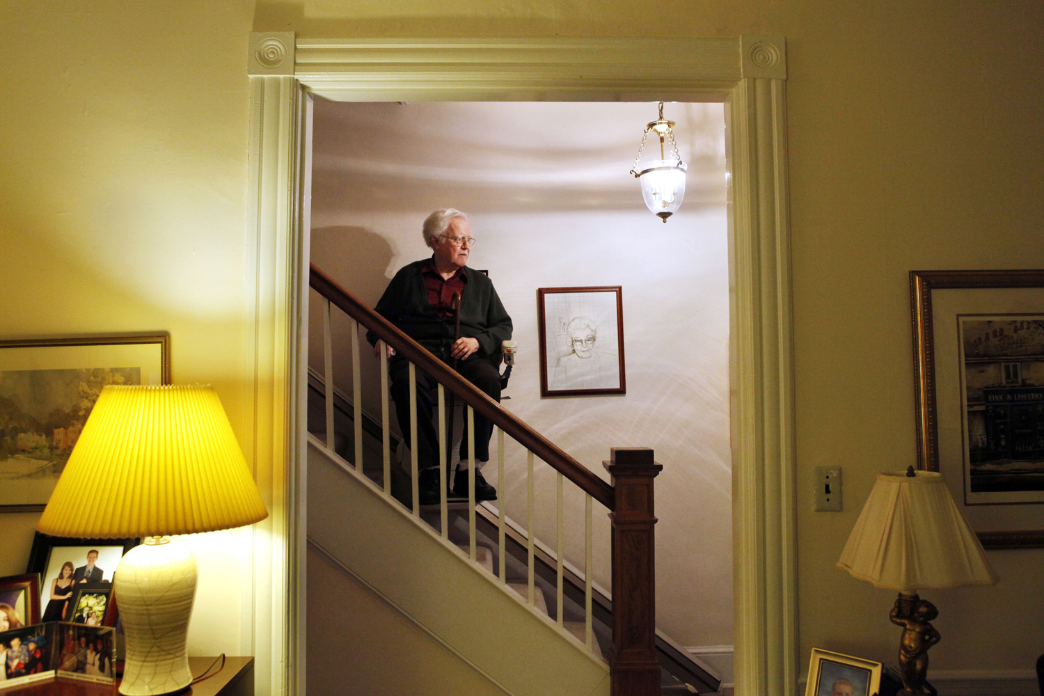 In this photo taken Oct. 12, 2011, Irving Lindenblad, 82, rides down the stairs assisted by a stair lift, at his home in Washington. (Jacquelyn Martin/AP)