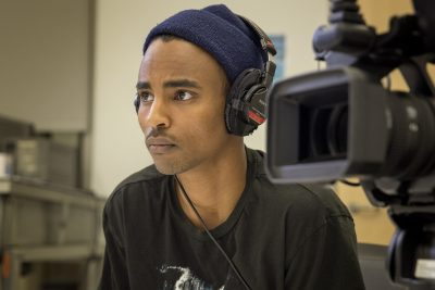 Filmmaker Abdirahman Abdi at UMass, conducting an interview for his film. (Robin Lubbock/WBUR)