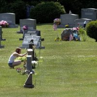 In this June 17, 2016 file photo, Erika Marble visits the gravesite of Edward Martin III, her fiancé and father of her two children, in Littleton, N.H. The 28-year old died Nov. 30, 2014, from an overdose of the opioid fentanyl. (Jim Cole/AP)