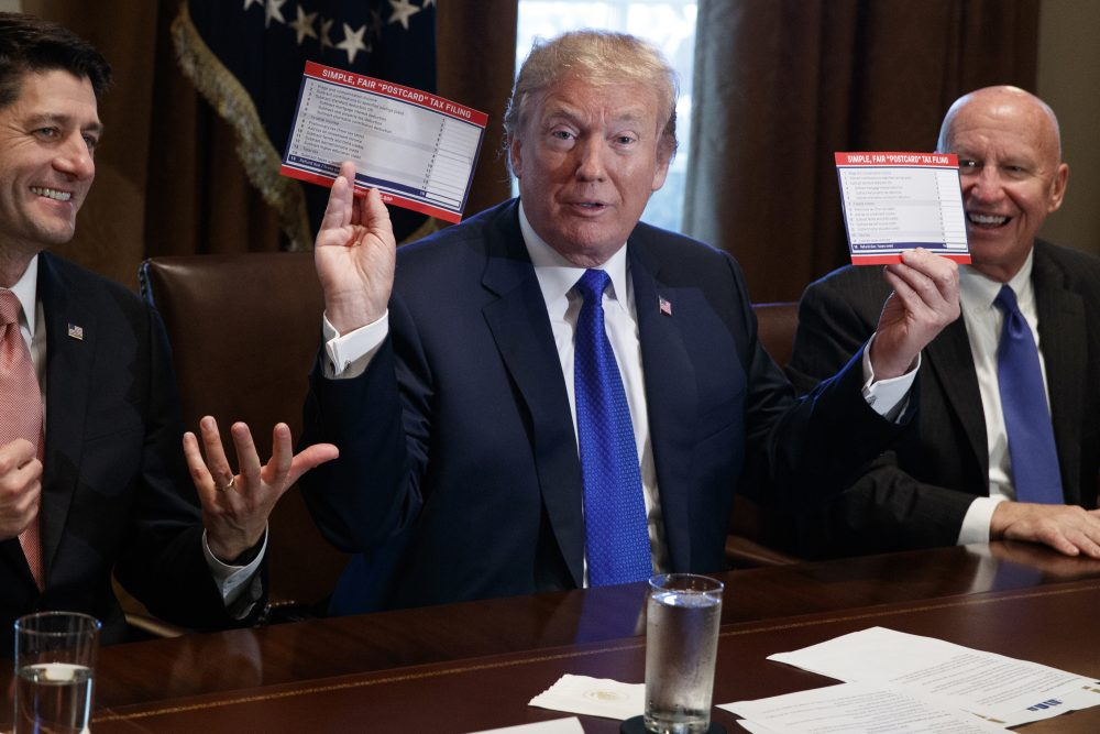 President Trump holds an example of what a new tax form may look like during a meeting on tax policy with Republican lawmakers including House Speaker Paul Ryan of Wis., and Chairman of the House Ways and Means Committee Rep. Kevin Brady, R-Texas, right, in the Cabinet Room of the White House, Thursday, Nov. 2, 2017, in Washington. (Evan Vucci/AP)