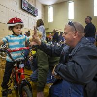 Five-year-old Christopher and Bob Charland celebrate with a high five after all the necessary adjustments have been made to his new bike so he can ride it. (Jesse Costa/WBUR)