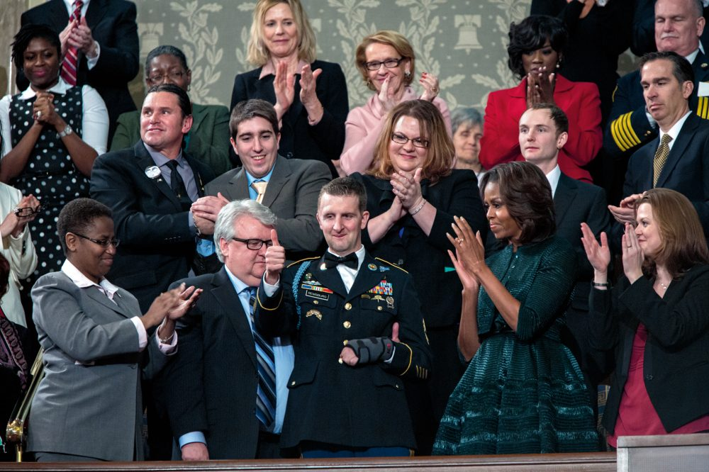 First lady Michelle Obama, Dr. Jill Biden and first lady's box guests acknowledge Army Ranger Cory Remsburg, who was recognized by President Obama in the State of the Union address in the House Chamber at the U.S. Capitol in Washington, D.C., Jan. 28, 2014. (Courtesy of Little, Brown and Company/Pete Souza)