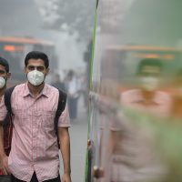 Indian commuters wear masks as they walk along a road amid heavy smog in New Delhi on Nov. 9, 2017. (Sajjad Hussain/AFP/Getty Images)