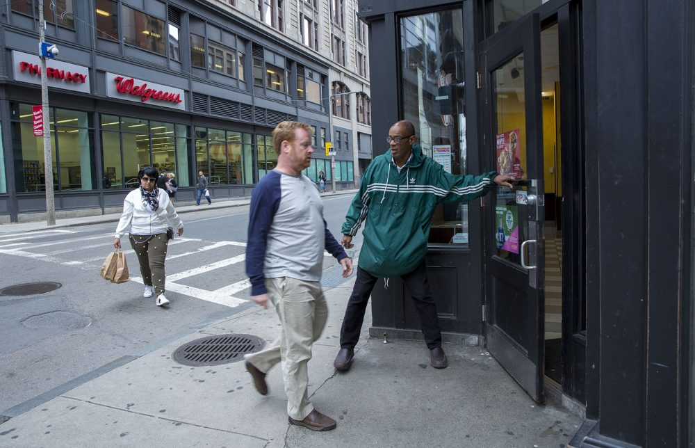 Higginbottom opens a door for someone while panhandling outside a Dunkin' Donuts in downtown Boston. (Robin Lubbock/WBUR)
