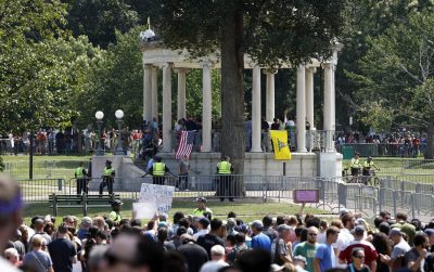 "Organizers stand on the bandstand on Boston Common during a self-described ""free speech"" rally in August. Throngs of counter-protesters stand along barricades separating them from the rally attendees. (Michael Dwyer/AP)"
