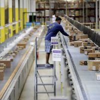 In this Tuesday, Aug. 1, 2017, photo, an Amazon employee makes sure a box riding on a belt is not sticking out at the Amazon Fulfillment center in Robbinsville Township, N.J. (Julio Cortez/AP)