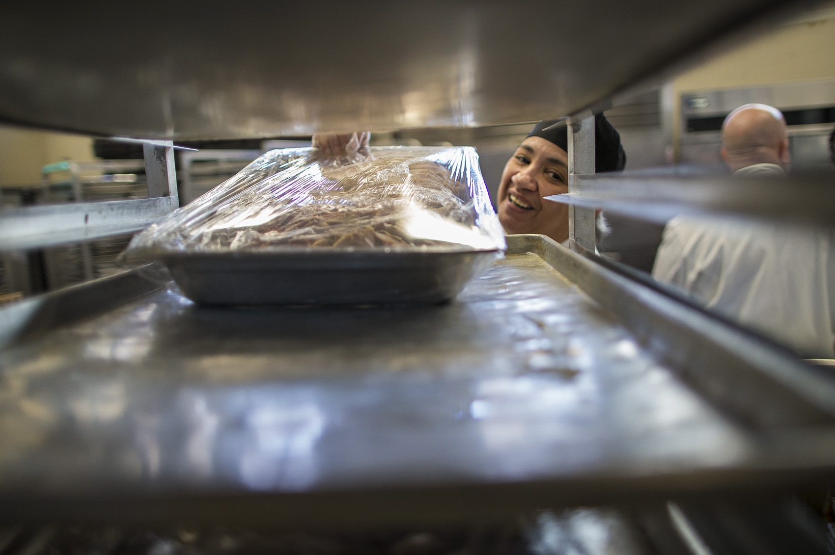 Eberidy Velazquez places a wrapped pan of turkey meat ready to be stored for Thanksgiving Day. (Jesse Costa/WBUR)