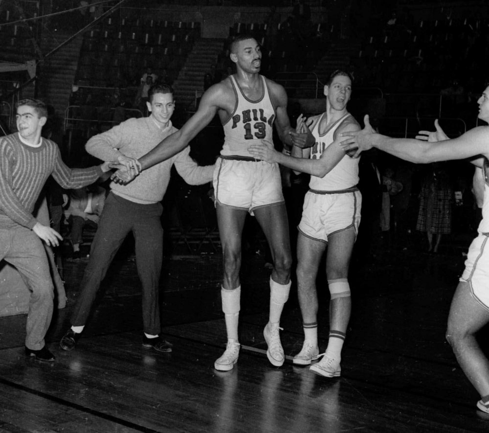 FILE - In this March 2, 1962 file photo, unidentified fans and teammates rush onto court to congratulate Philadelphia Warriors Wilt Chamberlain (13) in Hershey, Pa., after he scored his 100th point in a 169-147 win over the New York Knickerbockers.  For 50 years, Chamberlain's 100-point night has stood as one of sports magic numbers. (AP Photo/Paul Vathis, File)