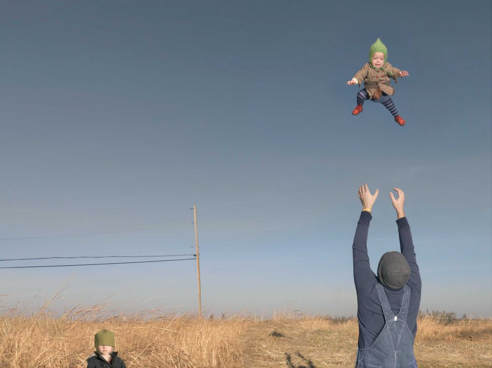 "Julie Blackmon's ""Baby Toss,"" taken in 2009. (Courtesy Elizabeth and Michael Marcus/Museum of Fine Arts, Boston)"