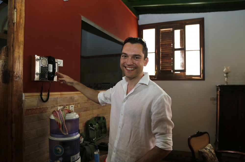 In this file photo from June 2015, co-founder of AirBnb Nathan Blecharczyk smiles to the camera as he points to an old telephone inside the guesthouse of Armando Usain in Havana, Cuba. (AP Photo/Desmond Boylan)