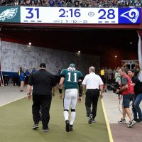Carson Wentz of the Philadelphia Eagles is escorted off the field after his injury. (Kevork Djansezian/Getty Images)