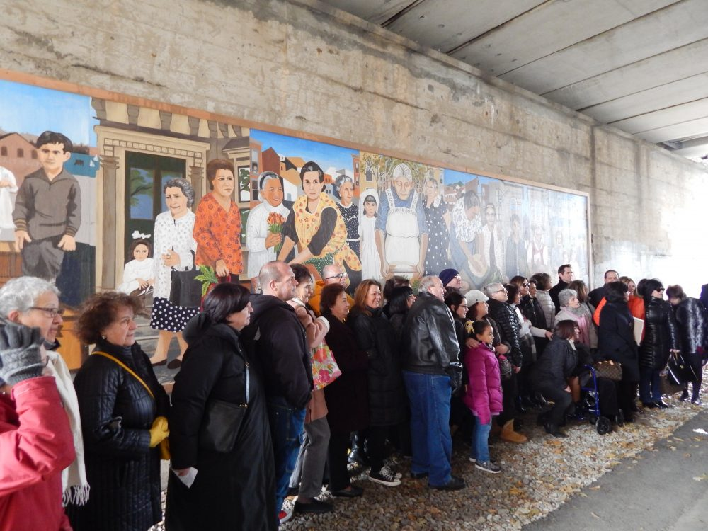 Families and friends of the grandmothers in the mural line up for the unveiling Friday morning. (Phaedra Scott/WBUR)