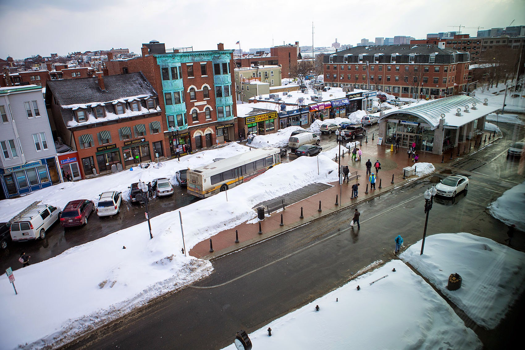 Between parked cars and snow banks, it's a tight squeeze for an MBTA bus in snow-filled Maverick Square in 2015. (Jesse Costa/WBUR)
