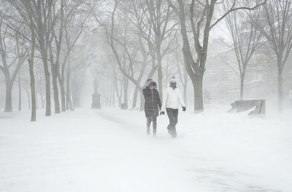 Shayla Walker and Hannah Leahey battle the wind and snow at they walk down Commonwealth Avenue in the snowstorm. (Robin Lubbock/WBUR)