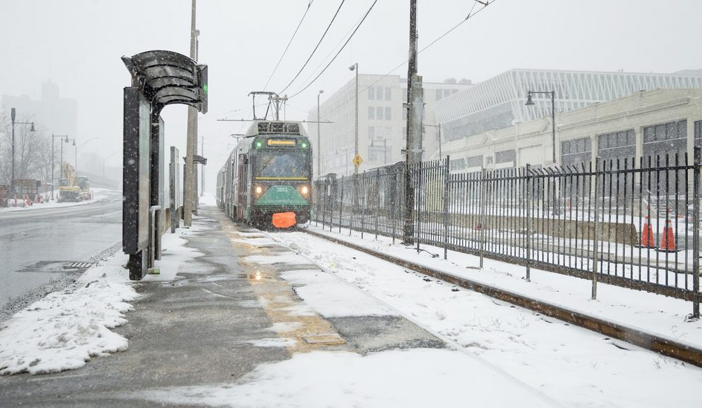 As snow falls at the start of the snowstorm, a Green Line train pulls into a deserted station on Commonweath Ave. (Robin Lubbock/WBUR)
