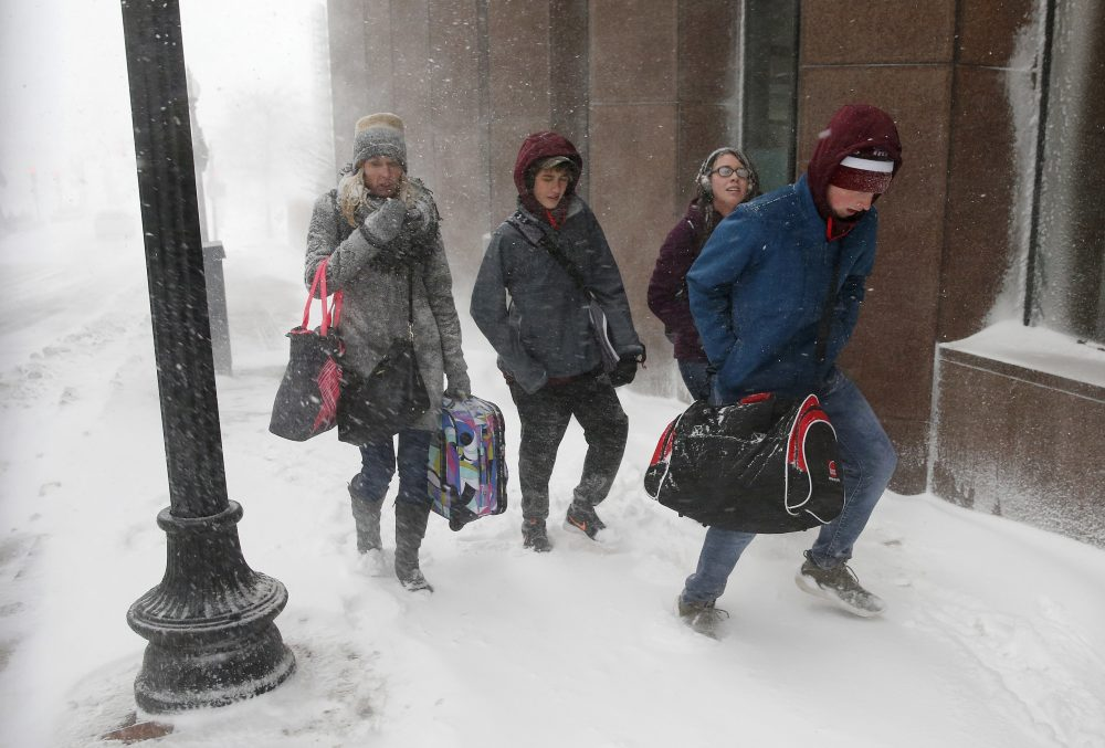 People with luggage walk through the snow in Boston. (Michael Dwyer/AP)