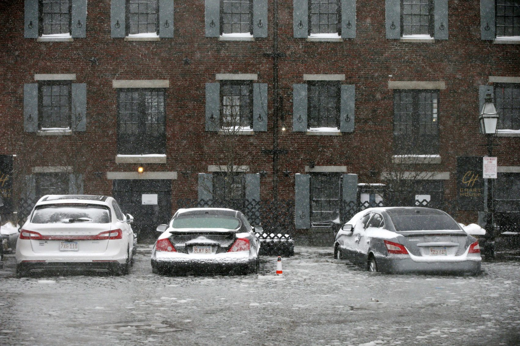 Cars sit in flood water from Boston Harbor on Long Wharf in Boston. (Michael Dwyer/AP)