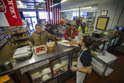 At the beginning of the morning rush, Jordan Hislop hands over a sandwich to a customer at DJ's European Market in Dorchester. (Jesse Costa/WBUR)