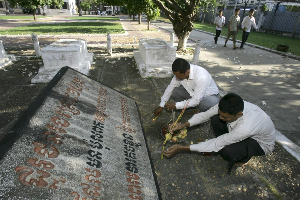 Cambodian officials pray at a grave site in the former Khmer Rouge prison complex, known as S-21, in Phnom Penh, Cambodia in 2009. Thousands of citizens perished in the notorious Tuol Sleng prison during the reign of the Khmer Rouge. (Heng Sinith/AP)