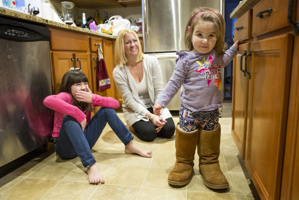 Rebecca tries on her mother's boots as her sister, Reagan, and mom, Beth Lacourse, look on. (Robin Lubbock/WBUR)