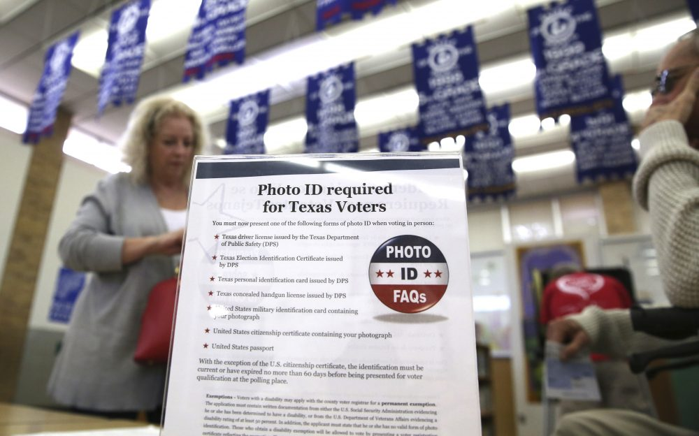 "In this March 1, 2016, file photo, a sign tells voters of voter ID requirements before participating in the primary election at Sherrod Elementary school in Arlington, Texas. Attorneys challenging tough voter ID laws in Texas and North Carolina say they'll keep pressing their lawsuits without the support of President Donald Trump's Justice Department if necessary. Trump announced Wednesday, Jan. 25, 2017, that he is ordering a ""major investigation"" into voter fraud, which tough laws requiring photo identification at the ballot box are designed to prevent. (LM Otero/AP)"