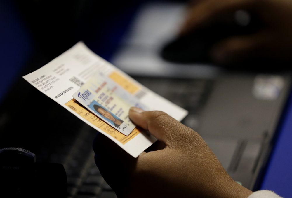 In this Feb. 26, 2014 file photo, an election official checks a voter's photo identification at an early voting polling site in Austin, Texas. (Eric Gay/AP)