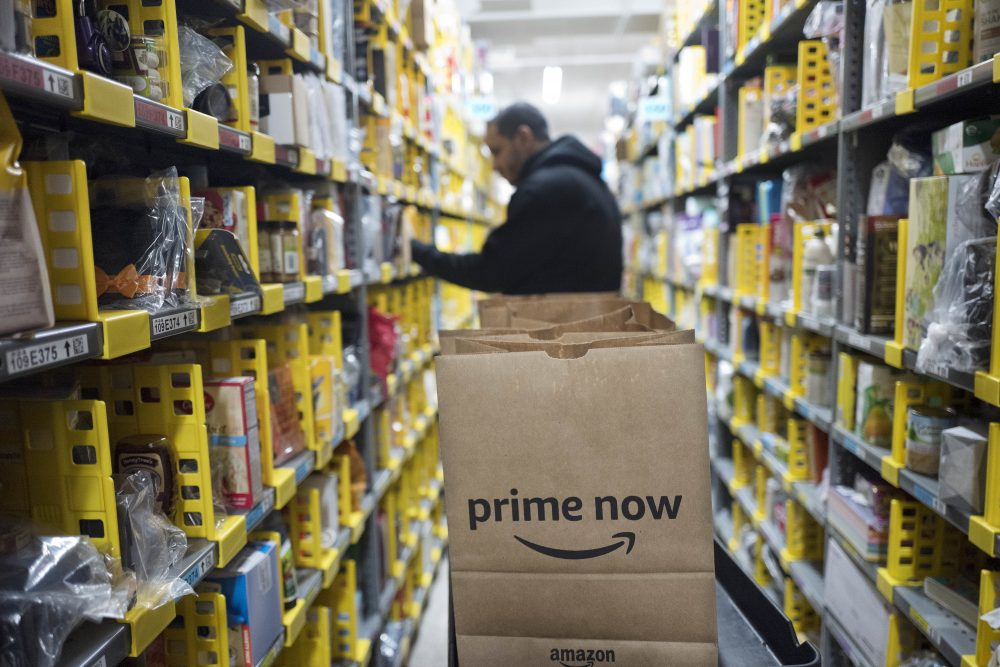 FILE - In this Wednesday, Dec. 20, 2017, file photo, a clerk reaches to a shelf to pick an item for a customer order at the Amazon Prime warehouse, in New York. Amazon announced Thursday, Jan. 18, 2018, that it has narrowed down its potential site for a second headquarters in North America to 20 metropolitan areas, mainly on the East Coast. (Mark Lennihan/AP)