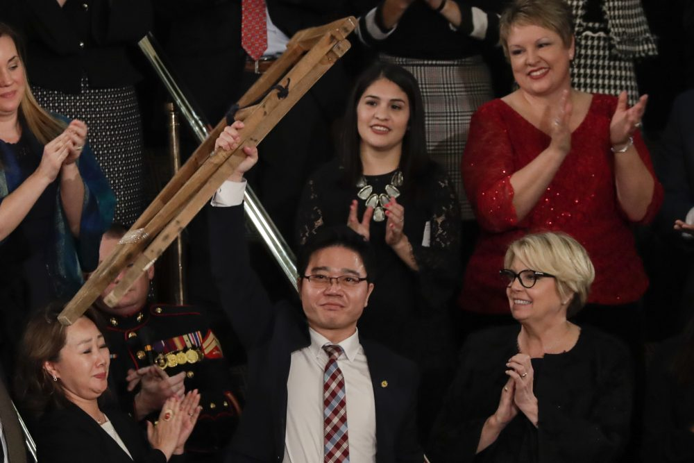 Ji Seong-ho holds up his crutches after his introduction by President Trump during the State of the Union address to a joint session of Congress on Capitol Hill in Washington, Tuesday, Jan. 30, 2018. (J. Scott Applewhite/AP)