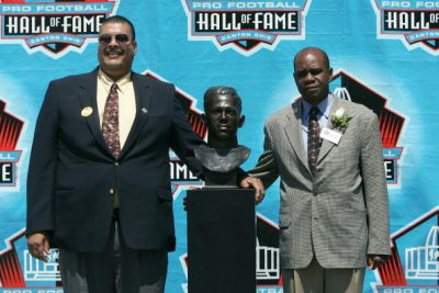 Fritz Pollard III (left) and Dr. Steven Towns pose with the bust of their grandfather, Fritz Pollard, during the 2005 NFL Hall of Fame induction ceremony in Canton, Ohio. (Jonathan Daniel/Getty Images)