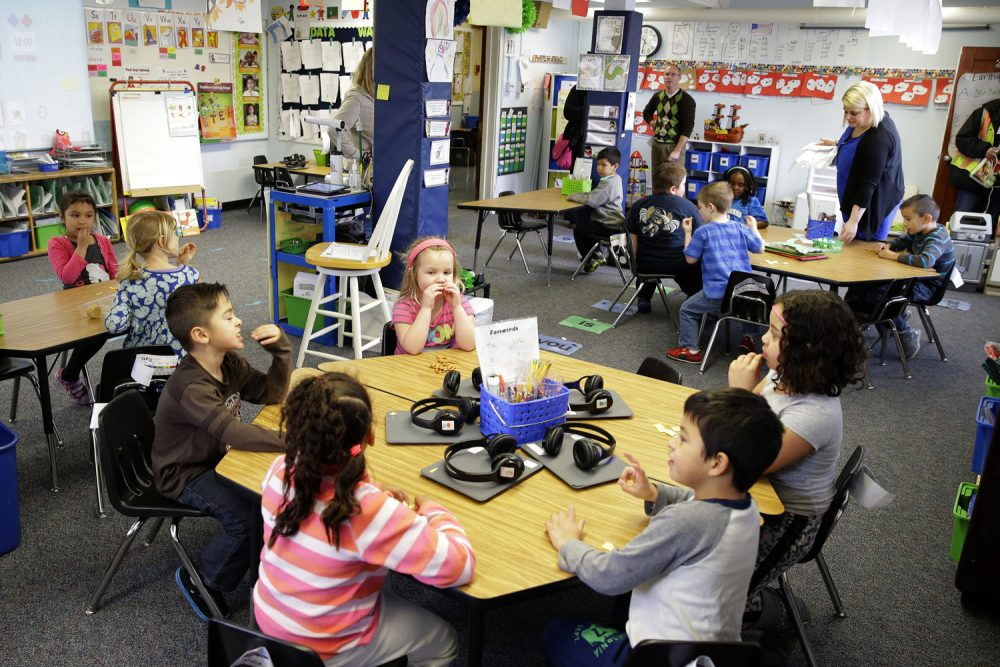 FILE - In this March 10, 2015, file photo, teacher Allison Williams, upper right, works with her kindergarten students at Des Moines Elementary School in Des Moines, Wash. The 2018 legislative session begins on Monday, Jan. 8, 2018, and lawmakers are hoping they'll finish their work including finalizing the last piece of a court mandate on education funding without having to go into overtime. (AP Photo/Ted S. Warren, file)