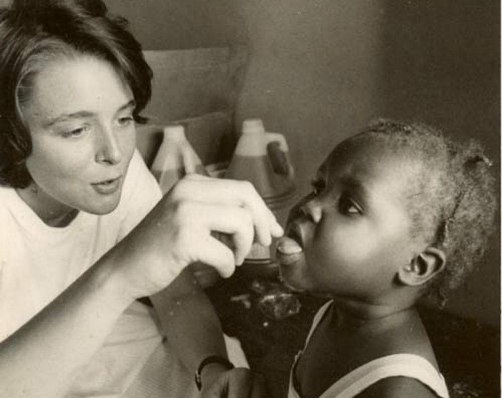 The author, pictured in the 1980s, gives a dose of medication to an unidentified Haitian girl. (Courtesy of Partners in Health)