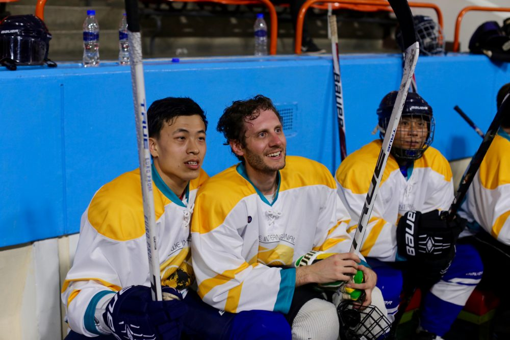 Alex sits with one of his newest linemates in his final contest in North Korea. (Courtesy Alex Frecon)