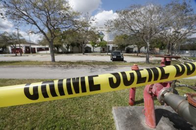 Crime scene tape runs outside Marjory Stoneman Douglas High School in Parkland, Fla., Sunday, Feb. 18, 2018. Authorities opened the streets around the school, which had been closed since a mass shooting on Wednesday. Nikolas Cruz, a former student, was charged with 17 counts of premeditated murder. (Gerald Herbert/AP)