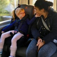 Brooke Adams, 4, cradles the face of Yolanda Brindis, her nurse, on the way to private preschool in Santa Rosa. The Rincon Valley Union School District covers the cost of the private placement, transports her there and provides Brooke's nurse. (Lee Romney/KALW)