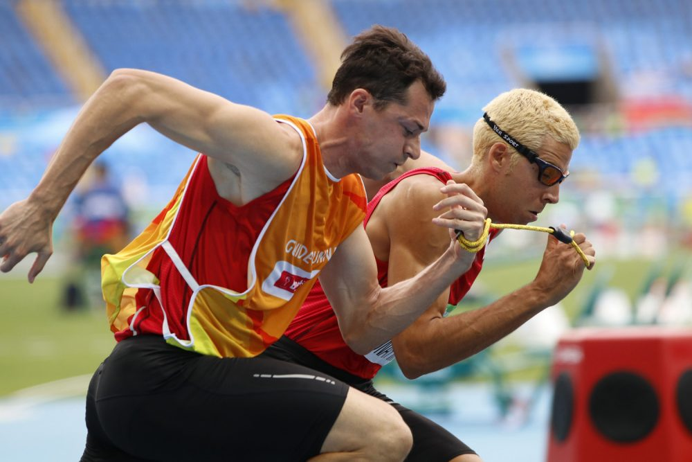 In this Thursday, Sept. 8, 2016 photo, Joan Lunar Martinez, right, of Spain and his guide Juan Enrique Valles Pastor compete in the men's 400-meter T12 first round, third heat at the 2016 Paralympic Games in Rio de Janeiro, Brazil, on. During the summer Paralympics, guides are used in cycling, equestrian, five-a-side soccer, triathlon and track and field events. (David A. Barnes/University of Georgia via AP)
