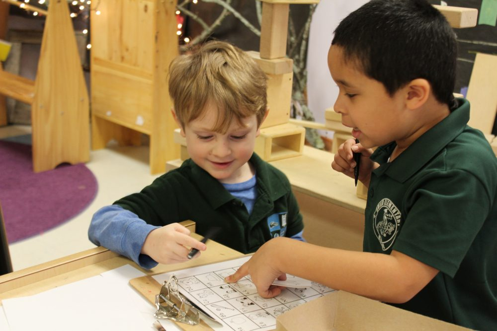 Kindergarten students Marco and Holden practice writing by labeling parts of a wolf they constructed in class. (Carrie Jung/WBUR)