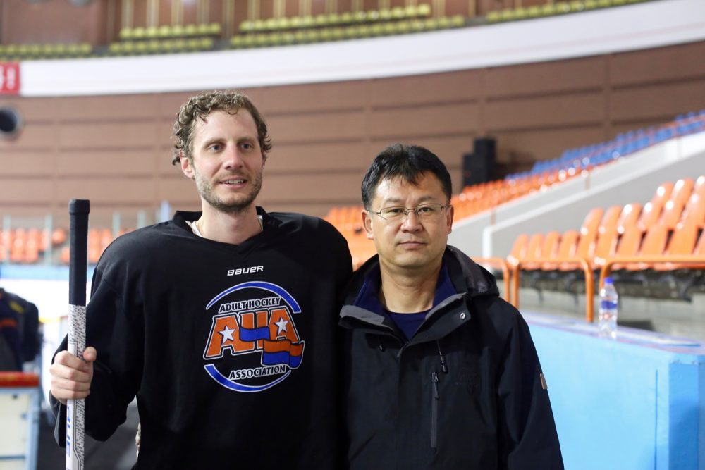 Alex stands rink-side in North Korea with the head coach of the men's national team, Yun Pong-chol. (Courtesy Alex Frecon)