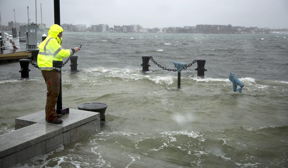 A man takes photographs as floodwaters surge at Boston's Long Wharf. (Robin Lubbock/WBUR)