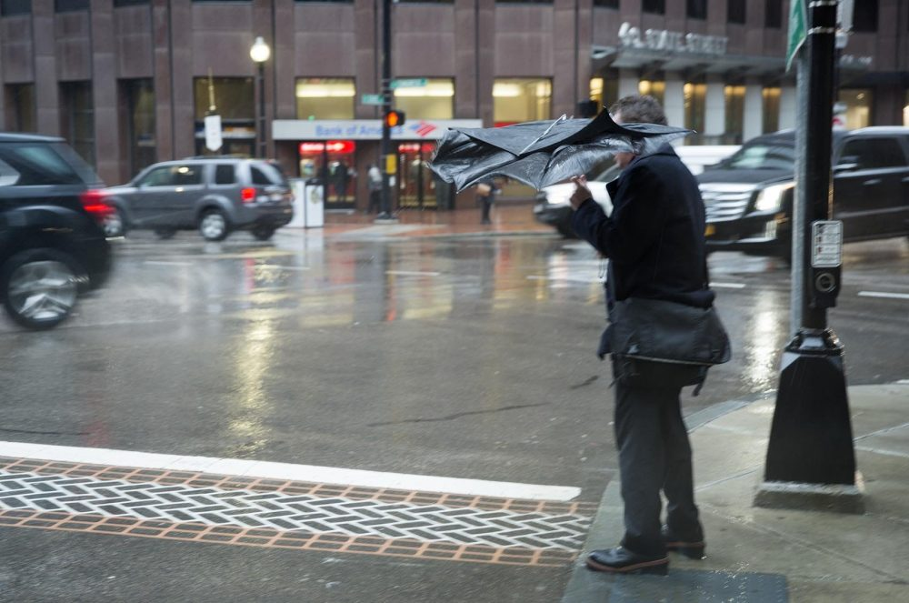 A gust of wind crumples this man's umbrella as he waits to cross State Street. (Robin Lubbock/WBUR)