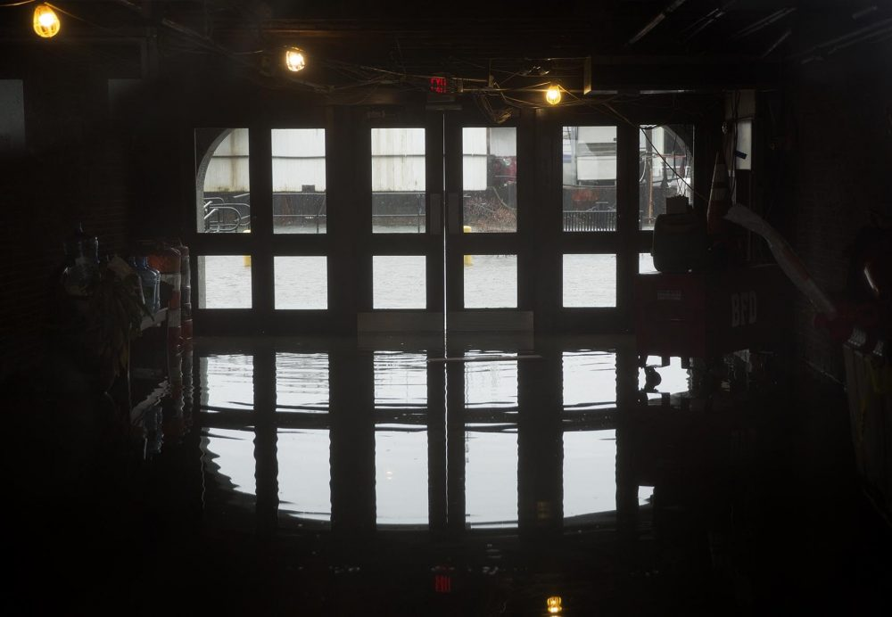 Flood waters seep under the doors of 66 Long Wharf. (Robin Lubbock/WBUR)