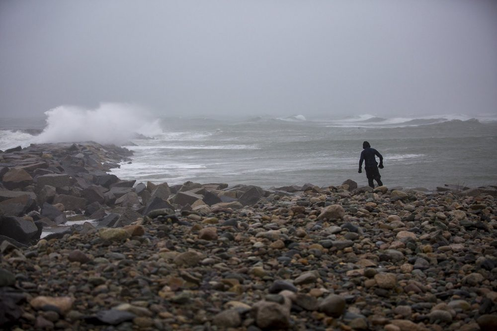 Brennan Kane, 12, braves the rain and high winds to walk out toward the sea wall at the Scituate Lighthouse. (Jesse Costa/WBUR)