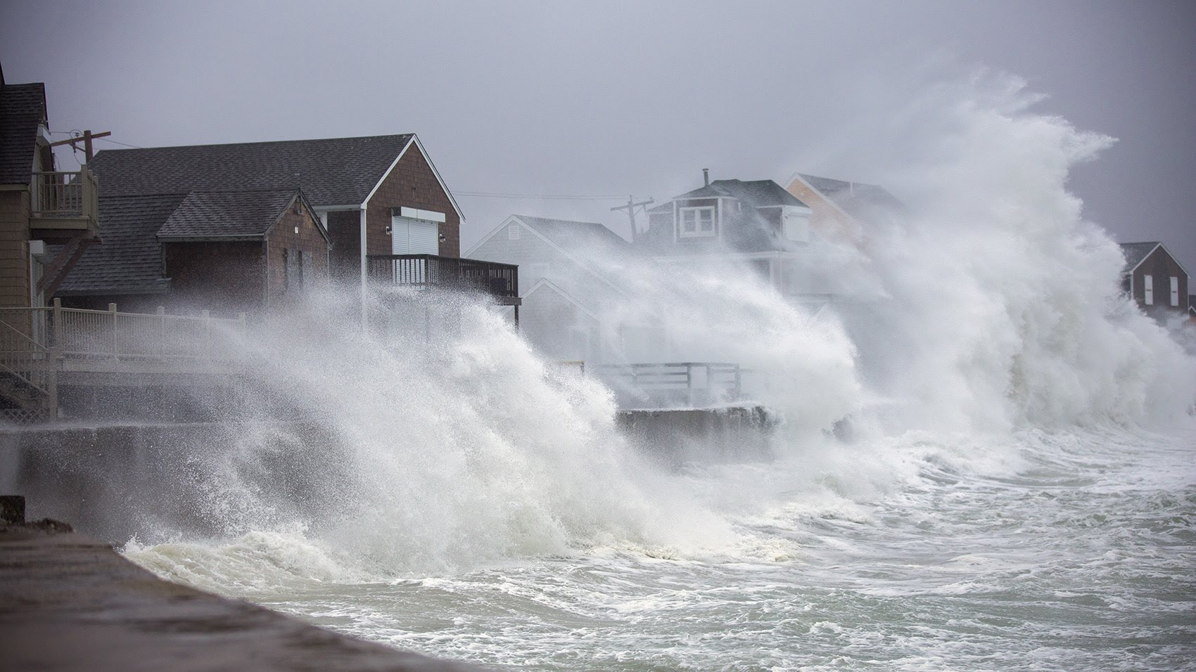 Houses along Lighthouse Road in Scituate are engulfed by waves crashing off the seawall. (Jesse Costa/WBUR)