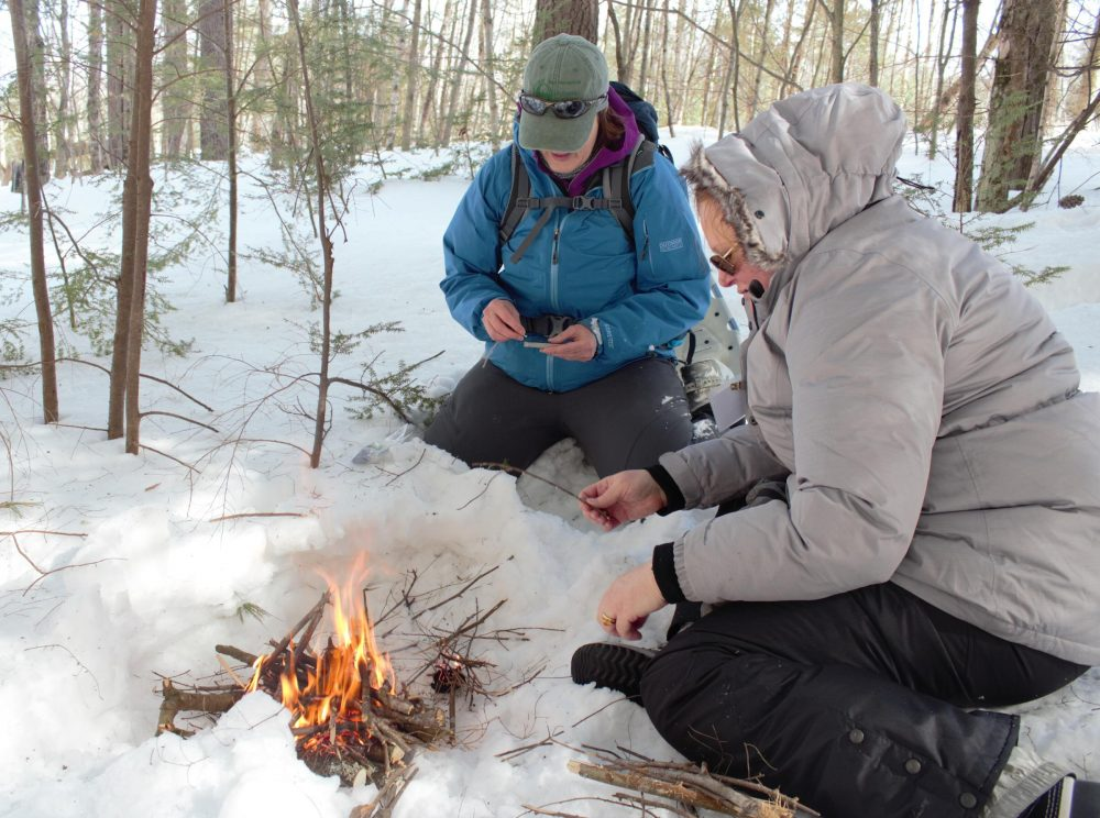 Julia Wilcox and Claire Rouge tend to a fire they made during BOW's winter survival skills class. (Annie Ropeik/NHPR)