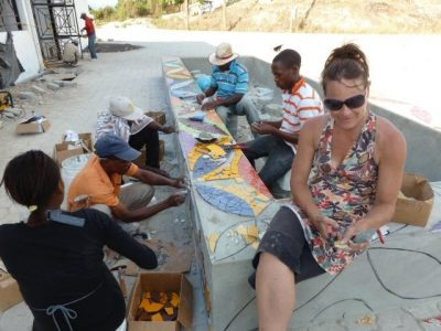 Laurel True at work with her team on a mosaic seat wall outside the Mirebalais hospital. (Courtesy Laurel True)