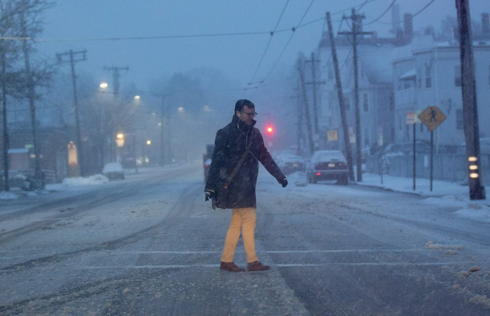 A man walks across Belmont Street in Cambridge as the snow begins to pick up in the early morning hours on Tuesday. (Jesse Costa/WBUR)