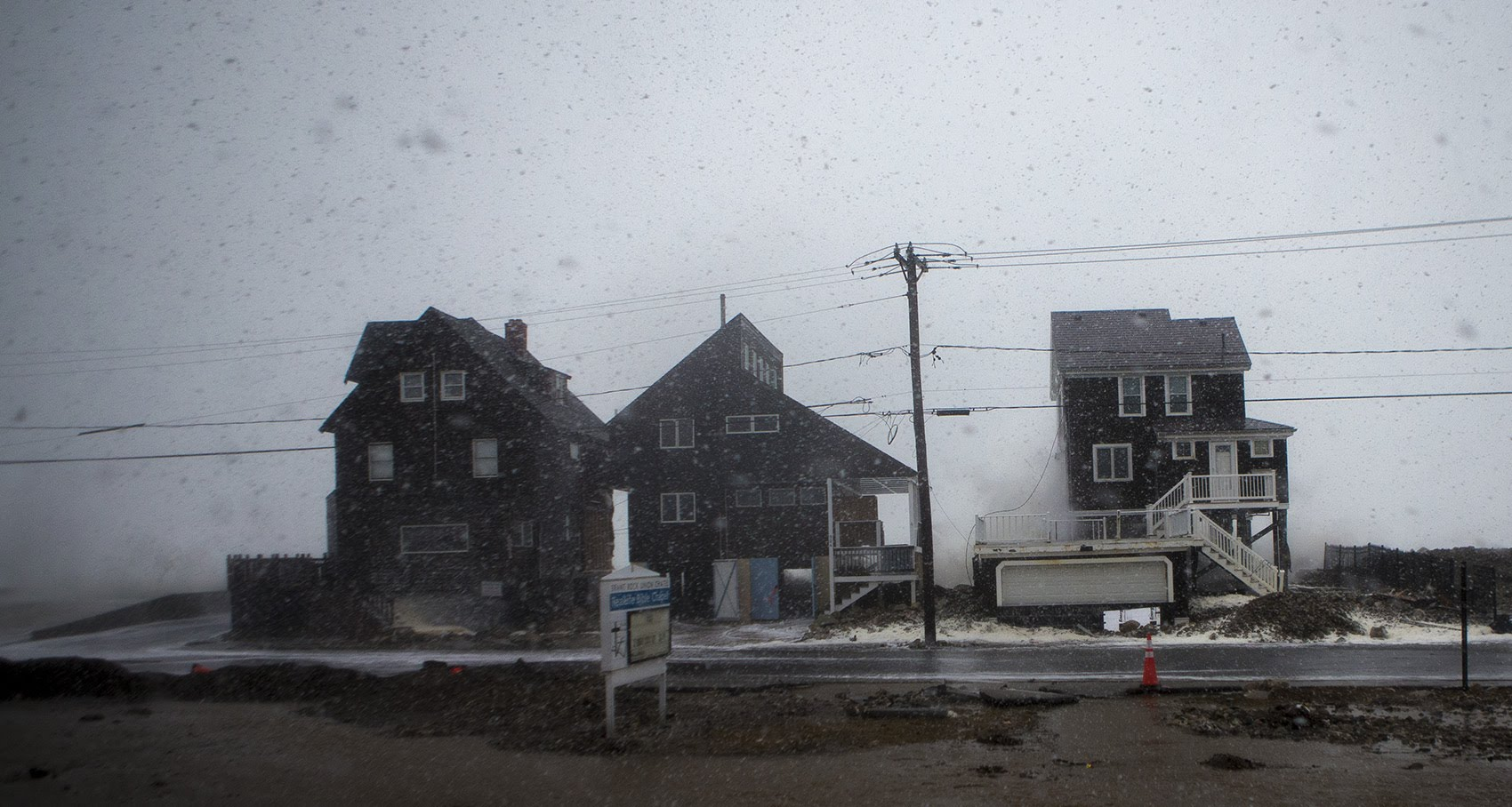 Waves crash along the seawall and houses on Ocean Street in Marshfield at high tide. (Jesse Costa/WBUR)