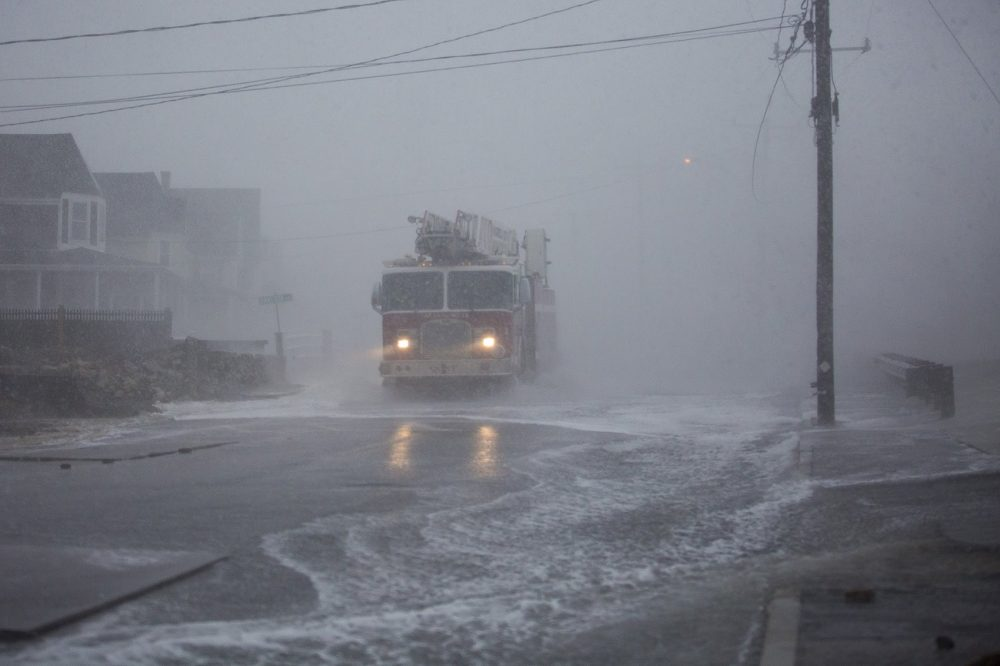 A Marshfield fire truck gets hit with wind and sea water from crashing waves on Ocean Street. (Jesse Costa/WBUR)